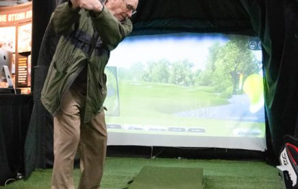 A Lifestyle show guest enjoying the Full Swing Golf simulator.